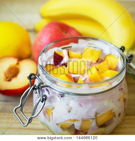 Fruit slices mixed with yogurt in a glass jar. Nectarine peach plum banana lemon and apple. Healthy eating concept. Square format