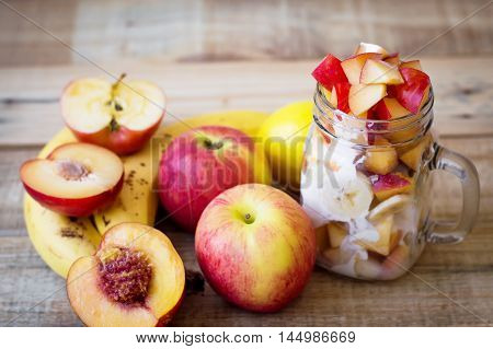 Fruit salad in a glass jar and variety of fruits on a wooden table. Apple banana plum peach nectarine and lemon