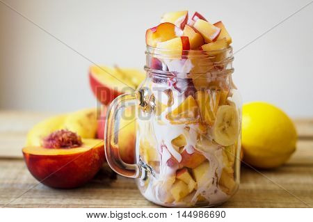 Fruit salad made of peach nectarine banana apple and lemon slices mixed with white yogurt on a wooden table