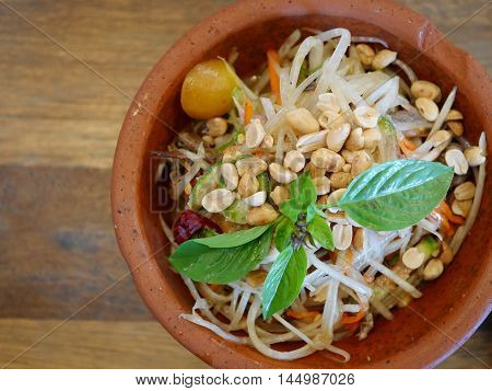 Papaya Salad (Som Tum) in pottery bowl on wooden background