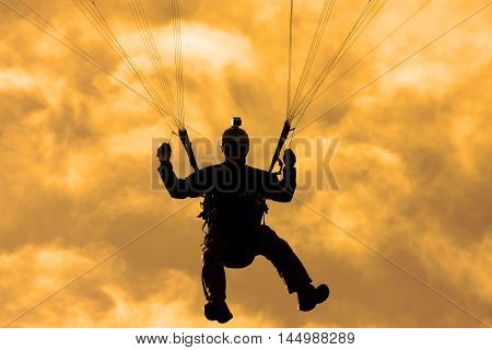 Paraglider in silhouette against an orange sky