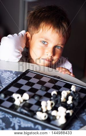 Little boy playing chess. Close-up portrait, bokeh