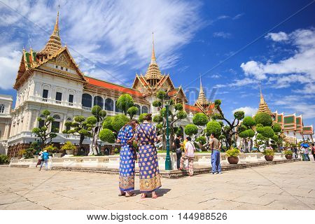 BANGKOK THAILAND - JUNE 29 : Unidentified tourists travel to Wat Phra Kaew and Grand Palace on June 29 2013 in Bangkok Thailand. Wat Phra Kaew is the most popular place for tourists to visit