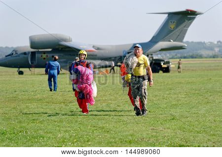 Kharkiv Ukraine - August 20 2016: Two skydivers carries a parachute on background of Antonov An-72 jet aircraft after landing at the airfield Korotych Kharkov region Ukraine on August 20 2016