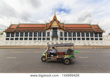 BANGKOK THAILAND - SEPTEMBER 21 2013: traditional tuk-tuk on the road in front of the famous Buddhist Temple Wat Phra Kaew one of the main landmarks of Bangkok Thailand