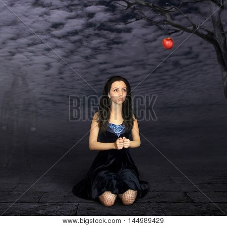 A girl is kneeling under a tree. She wants to disrupt the apple. But it is very dangerous. The devil is waiting for her.