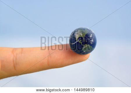 Hand holding earth on fingertip/ World at your Fingertips