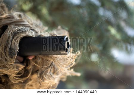 Black muzzle of gun covered with military ghillie mask on green trees in forest background closeup