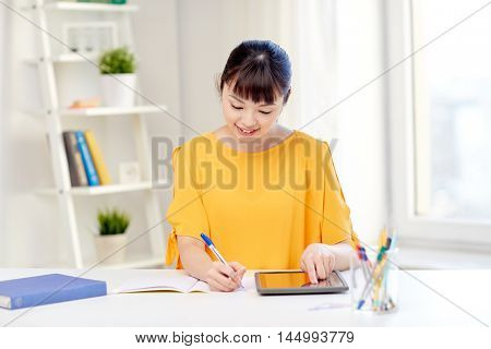 people, education, high school and learning concept - happy asian young woman student with tablet pc computer, book and notepad writing at home
