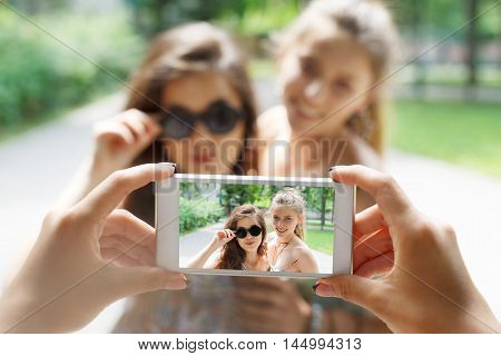 Two girls friends outdoors and someone POV view, taking photos at digital camera of smartphone. Young females at mobile screen, laughing and having fun in summer park. Lifestyle portrait.