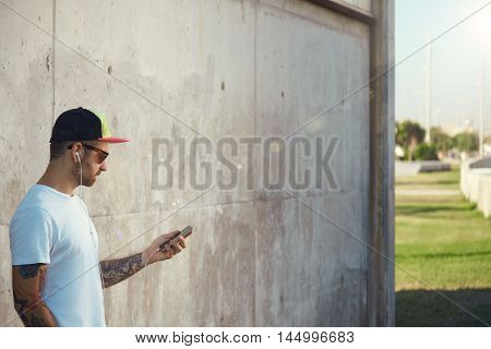 Bearded And Tattooed Young Man Holding His Smartphone