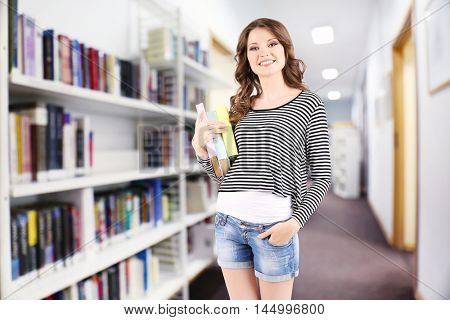 Young woman with stack of books on blurred book shelves background.