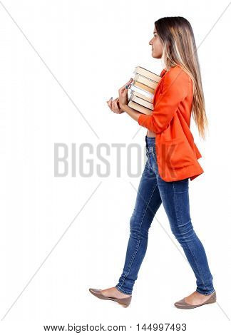 Girl comes with stack of books. side view. girl in a red jacket goes to the side with a stack of books.