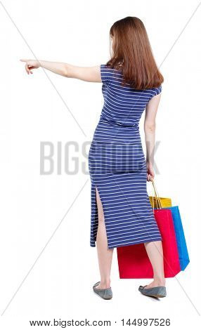 back view of woman with shopping bags pointing . brunette in a blue striped dress standing with shopping bags and showing thumb sideways.