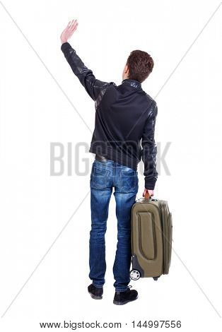 Back view of man with green suitcase man greeting waving from his hands. traveler is carrying a suitcase waving goodbye.
