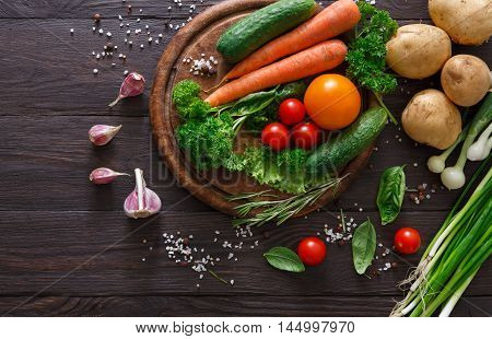 Desk with fresh organic vegetables on wood background. Healthy natural food abundance on rustic wooden table with copy space. Potato, garlic, onion, pepper and other cooking ingredients top view