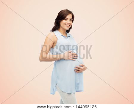 pregnancy, motherhood, people and expectation concept - happy pregnant woman touching her big belly over beige background
