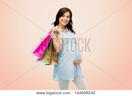 pregnancy, sale, motherhood, people and expectation concept - happy pregnant woman with shopping bags touching her big belly over beige background