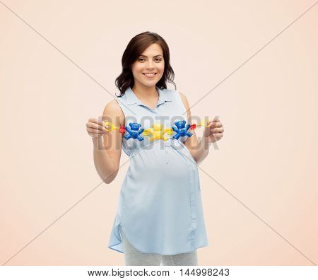 pregnancy, motherhood, people and expectation concept - happy pregnant woman holding rattle toy over beige background
