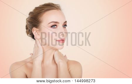 beauty, people and bodycare concept -beautiful young woman face and hands over beige background