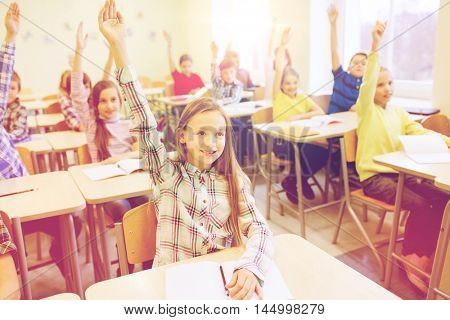 education, elementary school, learning and people concept - group of school kids with notebooks sitting in classroom and raising hands