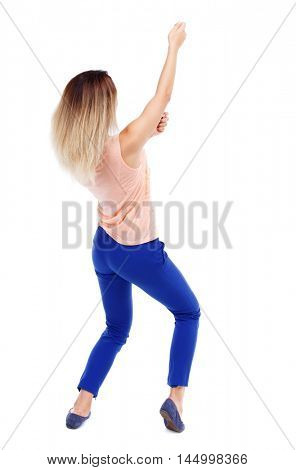 back view of standing girl pulling a rope from the top or cling to something. girl watching. Isolated over white background. Blonde in blue pants pulling a rope from the top.