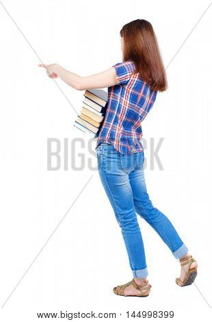 Girl carries a heavy pile of books. back view. Girl in plaid shirt cancer is holding a stack of books and pointing her finger sideways.