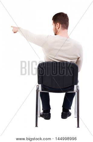 back view of young business man sitting on chair and pointing. bearded man in a white warm sweater sits on a chair pointing sideways.