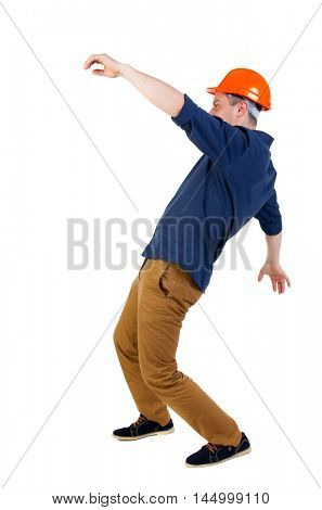 Balancing young man. or dodge the falling man. worker in construction helmet falls. Engineer in protective helmet falls waving his arms.