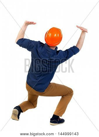 back view business man protective construction helmet protects hands from what is falling from above. engineer in a blue shirt with the sleeves rolled up and a helmet sat down under the weight of the