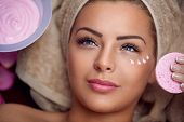 Pretty young woman with facial mask at beauty salon poster