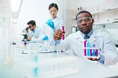 Waist up of male African-American scientist in lab coat and safety goggles looking at camera holding poster