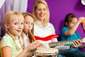 Family - Children and mother - making music; they are practicing playing guitar, bongo and flute