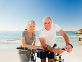 picture of retirement  - Retired couple with their bikes on the beach - JPG