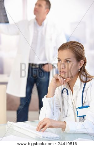 Young female doctor working on computer in office, male doctor in background.?