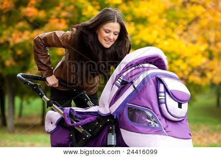 Happy Mom With Stroller Walks In Park
