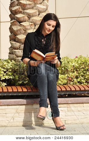 Young Beautiful Woman Reading A Book Sitting On Bench
