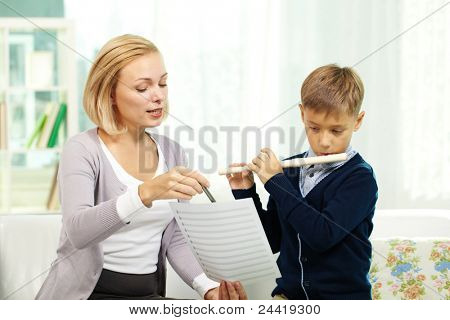 Portrait of pupil playing the flute while his tutor showing notes