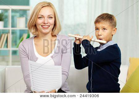 Portrait of happy pupil playing the flute with charming tutor near by