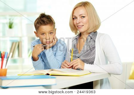 Portrait of pretty tutor and diligent pupil looking at camera