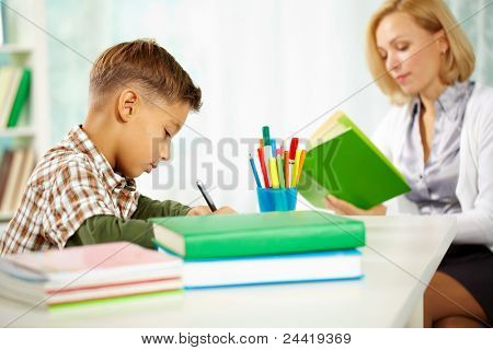 Portrait of diligent boy writing something with his tutor reading near by