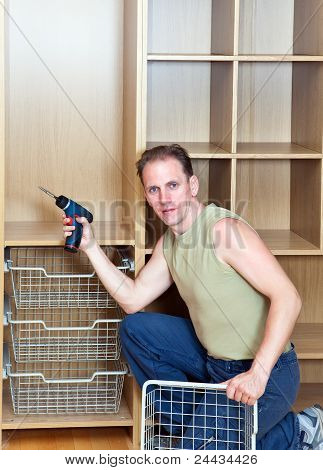The man is engaged in assemblage of a new wardrobe