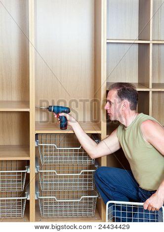 O homem é envolvido em Assembléia de reparo e de móveis