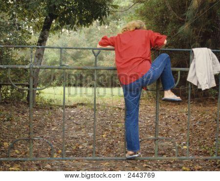 Woman Climbing Fence