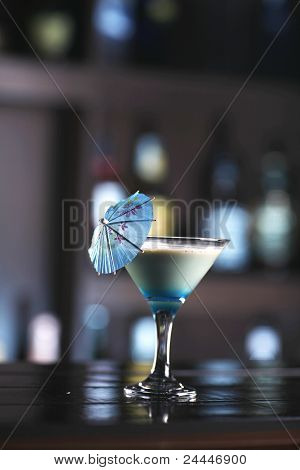 Beautiful Blue, Creamy Cocktail In A Martini Glass With A Blue Umbrella.
