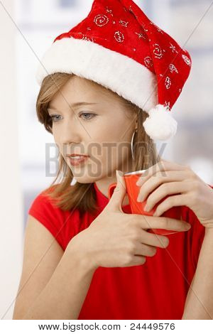 Portrait of attractive young woman, wearing red shirt and Santa Claus hat, holding cup.?