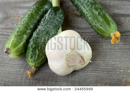 Green Cucumbers And Garlic On A Table