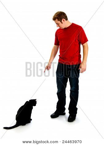 Bad Kitty - Man Pointing At A Black Cat With His Head Down.