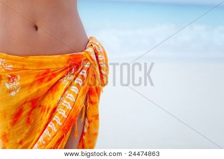 beach woman wearing an orange sarong outdoors