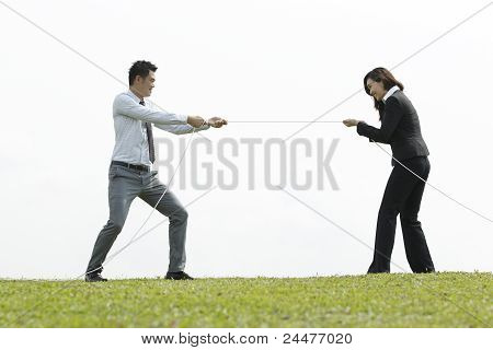Business Couple Playing Tug Of War
